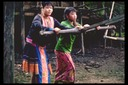 Hmong girls operating grist mill, Bua Chan, Thailand, 1986